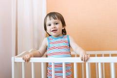 2 años felices de niño en la cama blanca Fotos de archivo