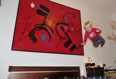 2 años felices de niño que salta en la cama Imagenes de archivo