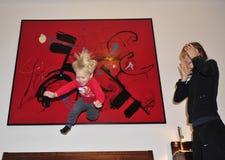 2 años felices de niño que salta en la cama Foto de archivo