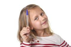 Años femeninos hermosos dulces del niño 6 a 8 que llevan a cabo concepto de las fuentes de escuela de la pluma de bola Fotografía de archivo