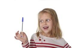 Años femeninos hermosos dulces del niño 6 a 8 que llevan a cabo concepto de las fuentes de escuela de la pluma de bola Foto de archivo libre de regalías