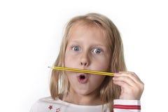 Años femeninos hermosos dulces del niño 6 a 8 que llevan a cabo concepto de las fuentes de escuela del lápiz Foto de archivo libre de regalías