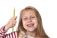 Años femeninos hermosos dulces del niño 6 a 8 que llevan a cabo concepto de las fuentes de escuela del lápiz Imagenes de archivo