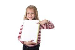 Años femeninos hermosos dulces del niño 6 a 8 que sostienen el cuaderno Foto de archivo libre de regalías