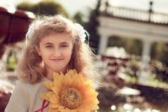 10 años hermosos de la muchacha que se coloca cerca de una fuente, sosteniendo a Foto de archivo
