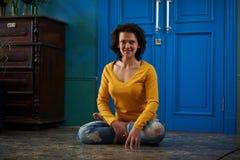 35 años hermosos de la mujer que se sienta en el asana Padmasana de la yoga - la actitud de Lotus en el cuarto del estilo del vin Imagen de archivo