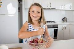 Años hermosos y adorables jovenes de la muchacha 6 o 7 que cocinan y que cuecen en casa la cocina que prepara la torta de la fres fotos de archivo
