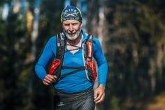 Años-hombre mayores sonrientes hermosos que corren a través del bosque Imagenes de archivo