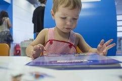 2 años inquisitivos del muchacho de historias de la ojeada en la biblioteca Fotografía de archivo
