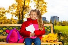 7 años lindos de la muchacha después de la escuela en parque del otoño Imágenes de archivo libres de regalías