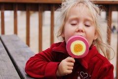 4 años lindos de la muchacha que come el helado Fotografía de archivo