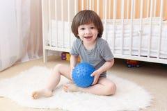 2 años lindos de muchacho con la bola de la aptitud Fotografía de archivo libre de regalías