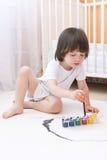 2 años lindos de muchacho con las pinturas del cepillo y del aguazo en casa Foto de archivo libre de regalías