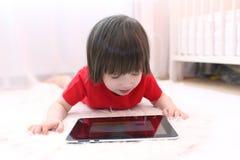 2 años lindos de muchacho en camiseta roja con la tableta en casa Foto de archivo
