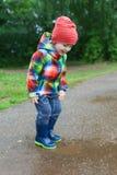 2 años lindos de muchacho en wellingtons que camina después de lluvia Imagen de archivo libre de regalías