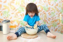2 años lindos de muchacho que cuece en casa la cocina Imágenes de archivo libres de regalías