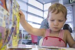 2 años lindos de muchacho que da vuelta a una página móvil del libro en la biblioteca Foto de archivo