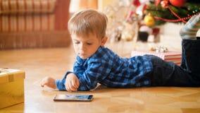 3 años lindos del niño pequeño que miente bajo el árbol de navidad e historietas de observación en el teléfono móvil foto de archivo