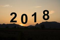 2018 Años Nuevos con el fondo de la puesta del sol y de la montaña Fotografía de archivo
