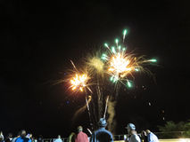 Años Nuevos de explosión de los fuegos artificiales en el aire como exhibición del reloj de la gente en Foto de archivo libre de regalías