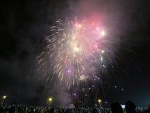Años Nuevos de explosión de los fuegos artificiales en el aire como exhibición del reloj de la gente en Imágenes de archivo libres de regalías