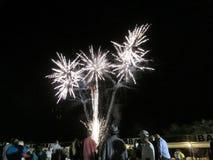 Años Nuevos de explosión de los fuegos artificiales en el aire como exhibición del reloj de la gente en Imagen de archivo libre de regalías