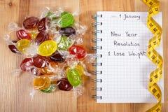 Años Nuevos de resoluciones escritas en cuaderno, caramelos y cinta métrica Foto de archivo