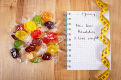 Años Nuevos de resoluciones escritas en cuaderno, caramelos y cinta métrica Imagen de archivo