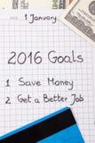 Años Nuevos de resoluciones escritas en cuaderno, las monedas dólar y tarjeta de crédito Foto de archivo libre de regalías