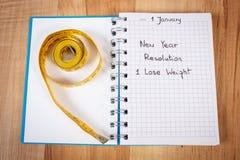 Años Nuevos de resoluciones escritas en cuaderno y cinta métrica Fotos de archivo libres de regalías