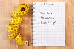 Años Nuevos de resoluciones escritas en cuaderno y cinta métrica Foto de archivo libre de regalías
