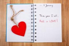 Años Nuevos de resoluciones escritas en cuaderno y corazón de madera rojo Foto de archivo