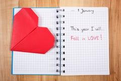 Años Nuevos de resoluciones escritas en cuaderno y corazón de papel rojo Fotos de archivo