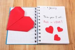 Años Nuevos de resoluciones escritas en cuaderno y corazones de papel rojos Fotos de archivo libres de regalías