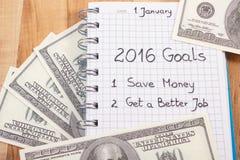 Años Nuevos de resoluciones escritas en cuaderno y dólar de las monedas Imagenes de archivo