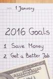 Años Nuevos de resoluciones escritas en cuaderno y dólar de las monedas Foto de archivo libre de regalías