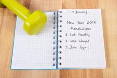 Años Nuevos de resoluciones escritas en cuaderno y pesas de gimnasia Imagen de archivo libre de regalías