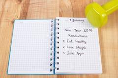 Años Nuevos de resoluciones escritas en cuaderno y pesas de gimnasia Fotografía de archivo libre de regalías