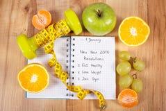 Años Nuevos de resoluciones escritas en cuaderno y pesas de gimnasia con centímetro Imagen de archivo