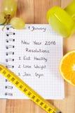 Años Nuevos de resoluciones escritas en cuaderno y pesas de gimnasia con centímetro Fotos de archivo