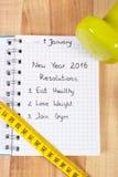 Años Nuevos de resoluciones escritas en cuaderno y pesas de gimnasia con centímetro Imagenes de archivo