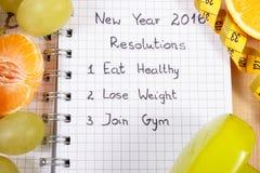 Años Nuevos de resoluciones escritas en el cuaderno y las frutas, pesas de gimnasia con centímetro Fotografía de archivo
