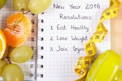 Años Nuevos de resoluciones escritas en el cuaderno y las frutas, pesas de gimnasia con centímetro Imagenes de archivo