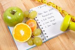 Años Nuevos de resoluciones escritas en el cuaderno y las frutas, pesas de gimnasia con centímetro Imagen de archivo libre de regalías