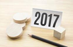 2017 Años Nuevos en tarjeta de visita con el pedazo redondo de madera en blanco y Imagenes de archivo