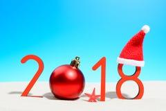 Años Nuevos festivos de concepto con la bola de la Navidad una playa tropical soleada con 2018 en rojo y espacio de la copia en u Fotografía de archivo