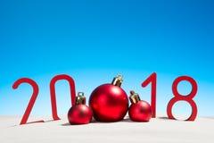 Años Nuevos festivos de concepto con las bolas de la Navidad una playa tropical soleada con 2018 en rojo y espacio de la copia en Fotos de archivo