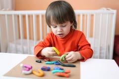 2 años preciosos de muchacho con el playdough en casa Imagen de archivo