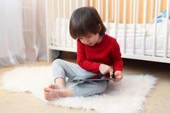 2 años preciosos de muchacho con la tableta Imágenes de archivo libres de regalías