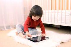 2 años preciosos de muchacho con la tableta en casa Fotos de archivo libres de regalías